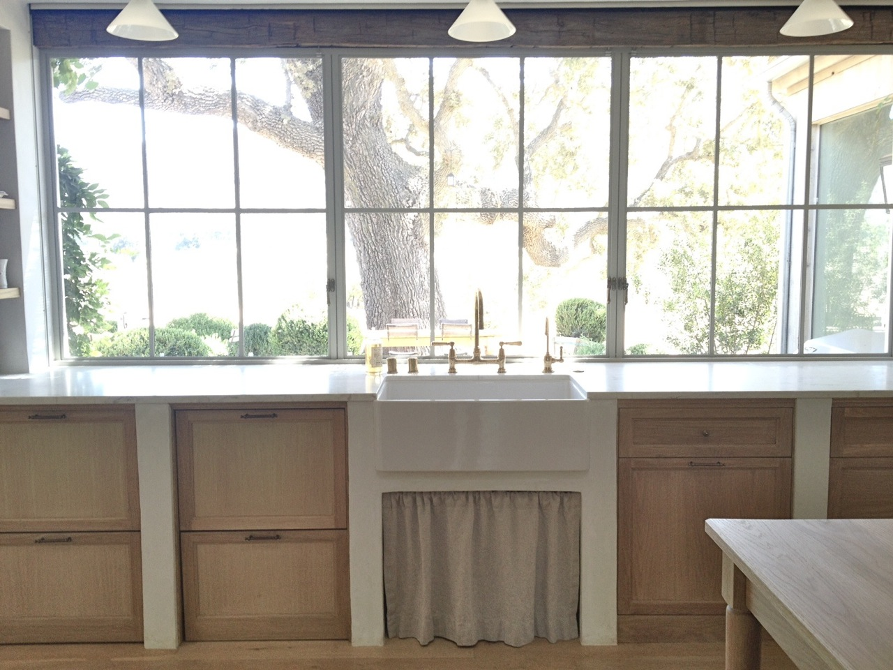 Glorious modern farmhouse kitchen with farm sink, white oak cabinetry, wall of windows, and linen skirt