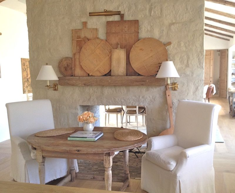 Cozy and charming hearth area with limestone fireplace and rustic mantel with breadboards at Patina Farm by Giannetti Home