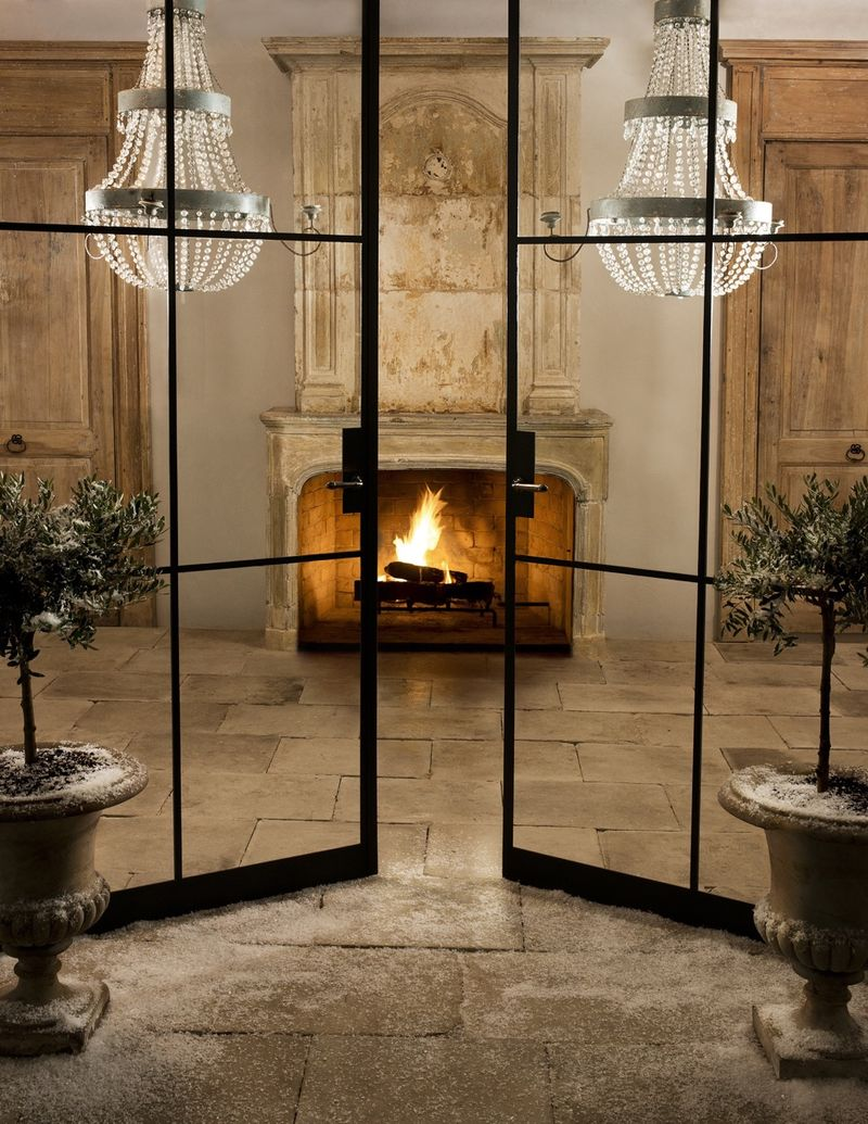 Chateau Domingue showroom with reclaimed stone floors, fireplace, and steel doors